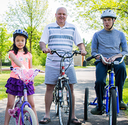 Louis McManus on his bike next to his father and sister.