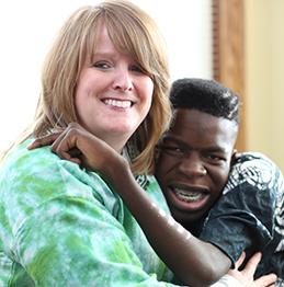 Karen wearing a green shirt hugs her son Moses
