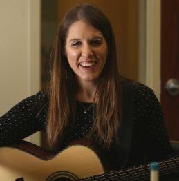 Neurologic Music Therapist, Laura Steines, holding a guitar